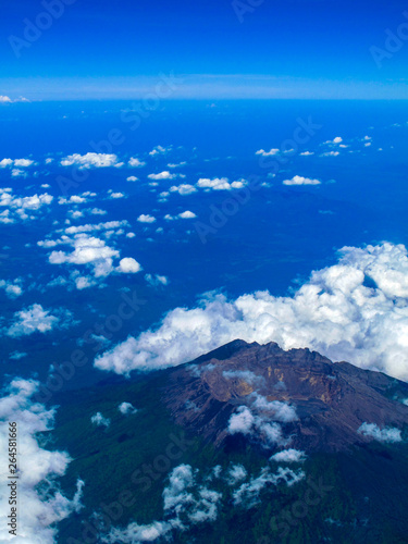 Inactive volcano in Indonesia with aerial view, surrounded by some clouds in a very bright blue sky day. #264581666