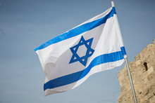 Flag Of Israel Against The Sky And The Wall
