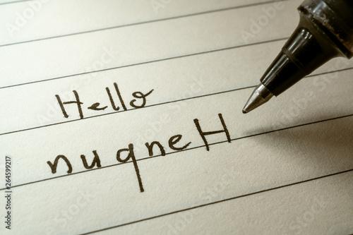 Photo Nerd lerning Klingon language writing Hello nuqneH word in Klingonese on a noteb