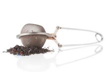 Old Tea Strainer With Black Tea On White Background