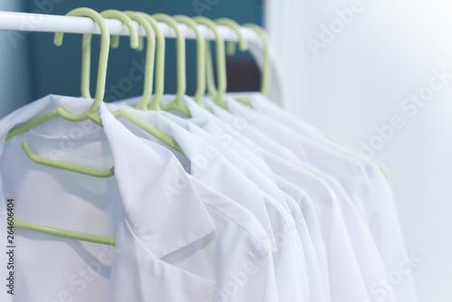 Fotografía  scrubs on hangers. Clean white coats for doctors. medical uniform
