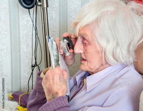 Valokuvatapetti Visually impaired elderly woman with magnifyer