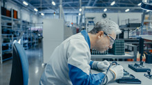 Senior Man In Blue - White Work Coat Is Using Plier To Assemble Printed Circuit Board For Smartphone. Electronics Factory Workers In A High Tech Factory Facility.
