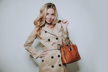 elegant cauccasian woman in beige coat holding brown bag