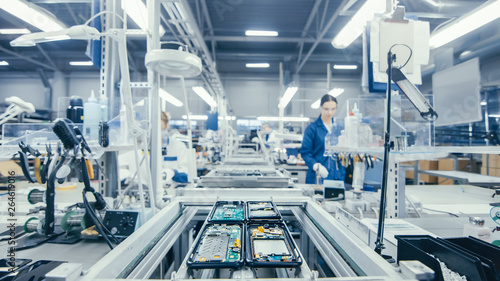 Photo Shot of an Electronics Factory Workers Assembling Circuit Boards by Hand While it Stands on the Assembly Line