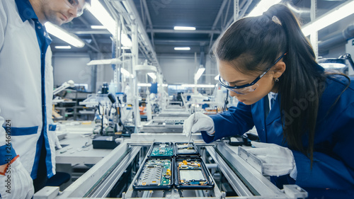 Stampa su Tela Shot of an Electronics Factory Workers Assembling Circuit Boards by Hand While it Stands on the Assembly Line