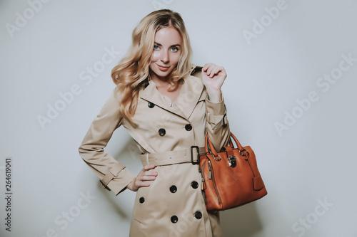 Obraz elegant cauccasian woman in beige coat holding brown bag - fototapety do salonu