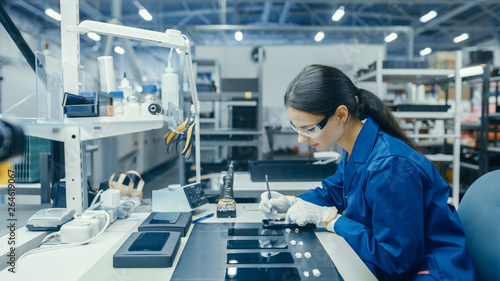 Fotografia  Young Female in Blue Work Coat is Assembling Printed Circuit Boards for Smartphones