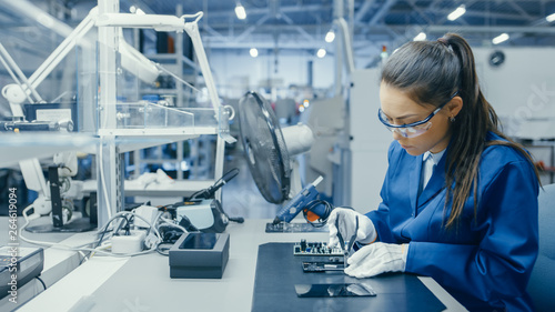 Carta da parati  Young Female Blue and White Work Coat is Using Plier to Assemble Printed Circuit Board for Smartphone