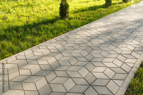 Fotografiet The footpath in the park is paved with diamond shaped concrete tiles
