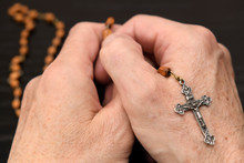 Hands Of Old Man Meditating And Praying On The Wood Beads Of A Holy Rosary With Crucifix