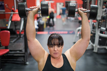 Strong Woman Lifting Weights A...