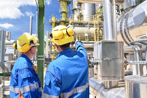 Fotografía  chemical industry plant - workers in work clothes in a refinery with pipes and m