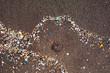 Spain, Canary Islands, Lanzarote, Playa Famara, microplastics, washed up on dark lava sand