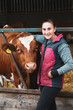 Young woman standing next to Guernsey cow on a farm.,Dairy Farm