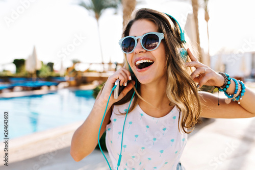 Fotografie, Obraz  Close-up portrait of excited curly tanned girl in trendy sunglasses walking by swimming pool outside
