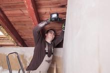 Roof Insulation, Worker Drilli...