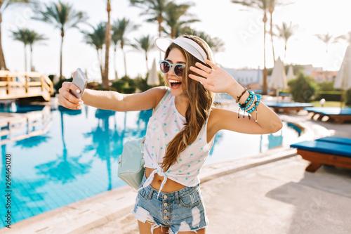 Pinturas sobre lienzo  Graceful dancing girl in trendy bracelets and white hat making selfie before swimming in open-air pool