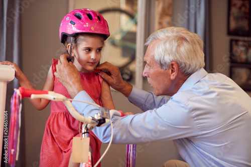 Papiers peints Individuel senior man buying new bicycle and helmets for little child.