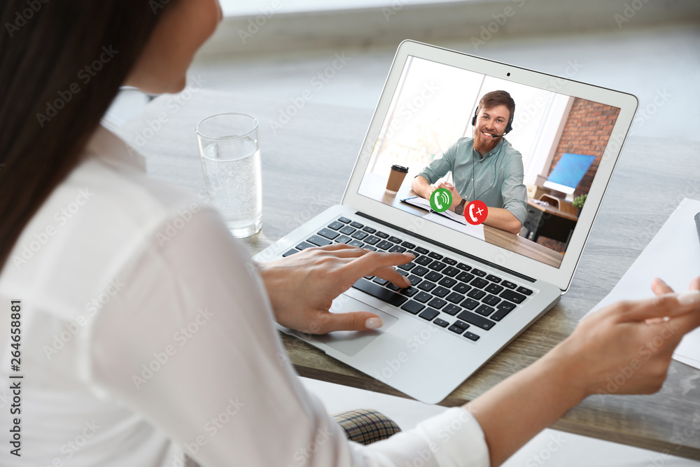 Fototapeta Woman having video chat with colleague at table in office, closeup