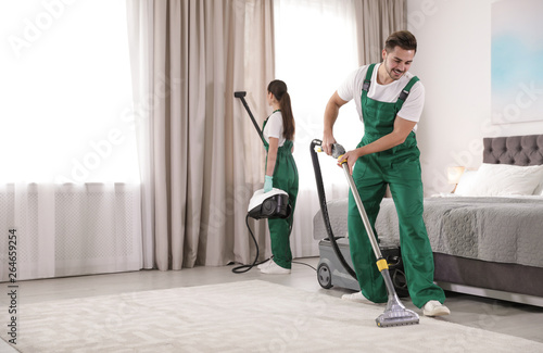 Pinturas sobre lienzo  Team of janitors cleaning bedroom with professional equipment