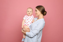 Portrait Of Happy Mother With Her Baby On Color Background