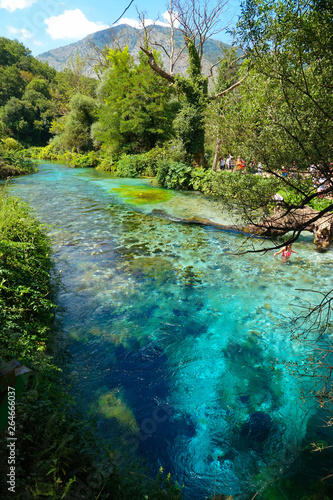 Tourists walk along the breathtaking turquoise colored river in national park Wallpaper Mural