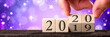 canvas print picture Hand Changing Date From 2019 To 2020 On Wooden Cube Calendar With Purple Background And Sparkles / New Year's Concept
