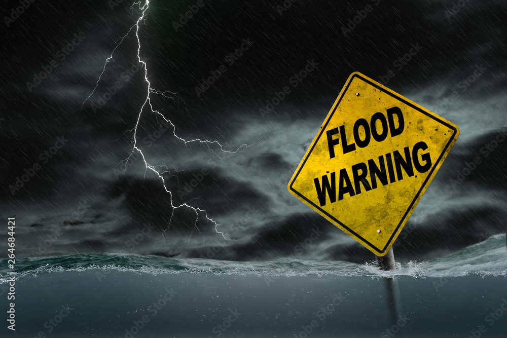 Fototapeta Flood Warning Sign Submerged in Rising Water With Stormy Background