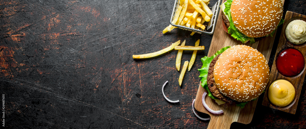 Fototapety, obrazy: Burgers with fries and various sauces.