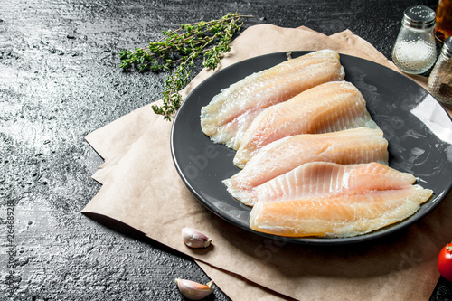 Fotografering Fish fillet on plate with paper, thyme and garlic cloves.