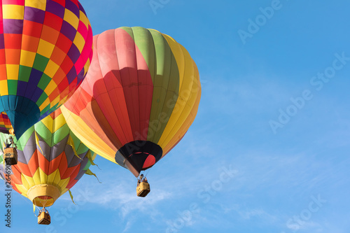 Fotografiet Three multi colored hot air balloons flying close to each othe over blue sky