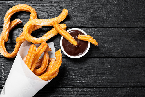Churros with sugar and chocolate sauce on black wooden background Wallpaper Mural