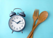 Time To Lose Weight , Eating Control Or Time To Diet Concept , A Alarm Clock Decoration On Blue Background