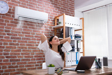 Businesswoman Enjoying The Cooling Of Air Conditioner