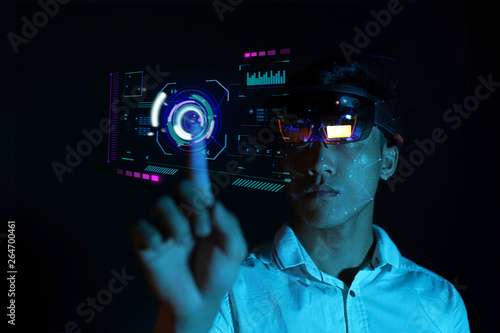 Photo  Business man try vr glasses hololens in the dark room | Young asian boy experien