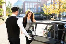 Chauffeur Opening Door For Businesswoman