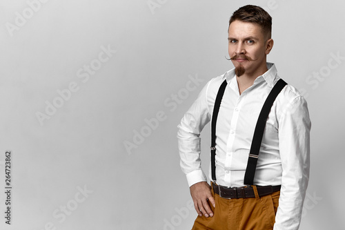 8667e6600d9 Attractive manly young Caucasian man with handlebar mustache and goatee  beard dressed in trendy clothes posing