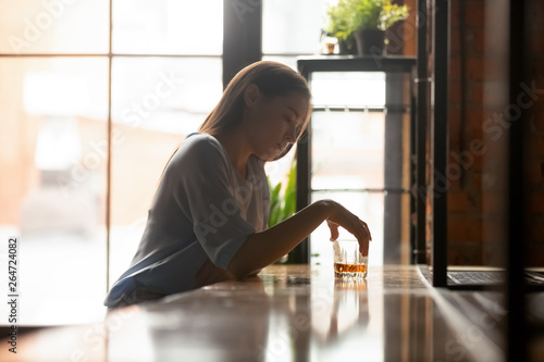 Photo Young sad woman sitting on bar counter drinking alcohol drinks