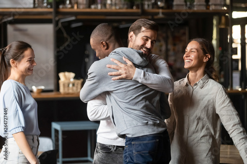 Fotografie, Obraz  Diverse guys best friends hugging greeting each other at meeting