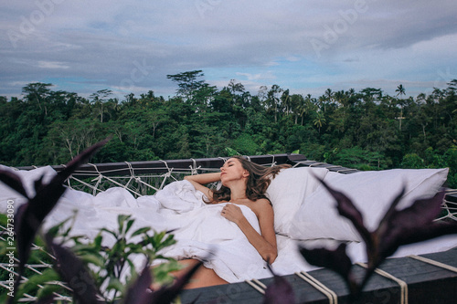 Poster de jardin Kiev beautiful woman with dark hair relaxing in open air bed with Bali jungle view