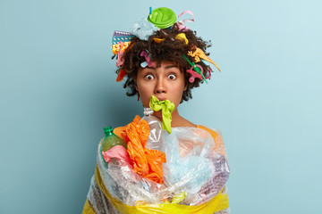 Volunteer woman says no to plastic pollution, demands save humanity, cleans rubbish, wrapped in polythylene sheeting, has rubber glove in mouth, stares with eyes popped out, isolated on blue wall