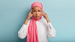 Leinwandbild Motiv Disappointed hopeless ethnic girl touches temples with finges, has headache, wears white shirt and pink hijab, has stressed facial expression, stands against blue background, needs pills from migraine