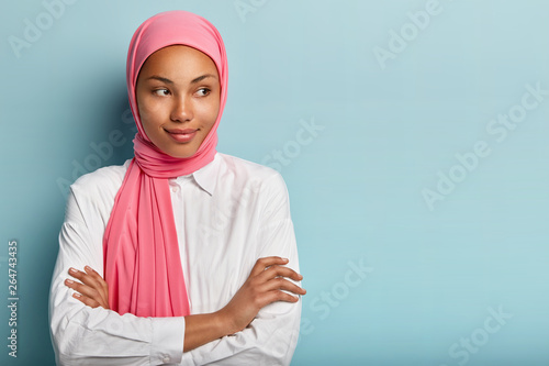 Photo Religious satisfied female model has arms folded, looks aside, has pleased expre