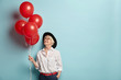 canvas print picture - Indoor shot of pleasant looking cheerful woman of old age holds helium air balloons, comes on party for elderly people to congratulate her best friend, focused above, wears fashionable clothes