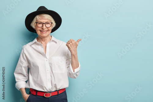 Fototapeta Waist up shot of friendly looking senior lady in stylish headgear, white elegant shirt and formal trousers, holds hand in pocket, points thumb away, has happy smile, advertises something nice obraz
