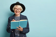 Portrait Of Pleased Female Pensioner Writes Plan Strategy In Diary, Has Nice Clever Look, Wears Glasses And Black Hat, Isolated Over Blue Studio Wall With Empty Space. Businesswoman With Notepad