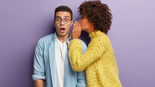 Photo Of Afro American Woman Whispers Secret To Boyfriend, Tells Shocking News. Astonished Young Man Keeps Jaw Dropped From Surprisement, Hears Terrible Rumors, Isolated Over Purple Background
