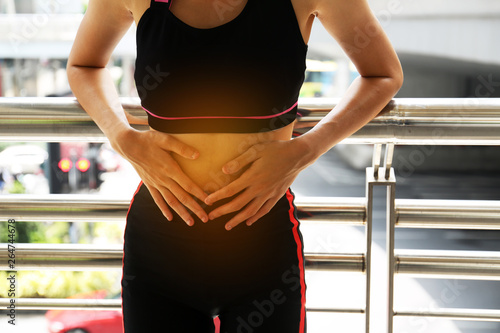 Fotomural Female athletes, abdominal pain, menstrual period during exercise on walking street in the city