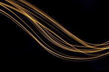 Long Exposure, Light Painting Photography.  Vibrant Streaks Of Metallic Gold Colour Against A Black Background